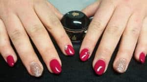 Acrylnägel in Rot und Glitzer dazu Steinchen als Nailart